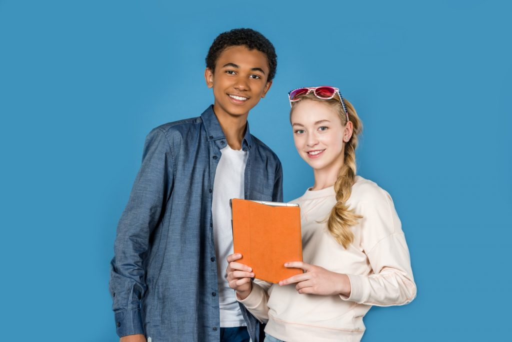 stylish happy teens with tablet isolated on blue