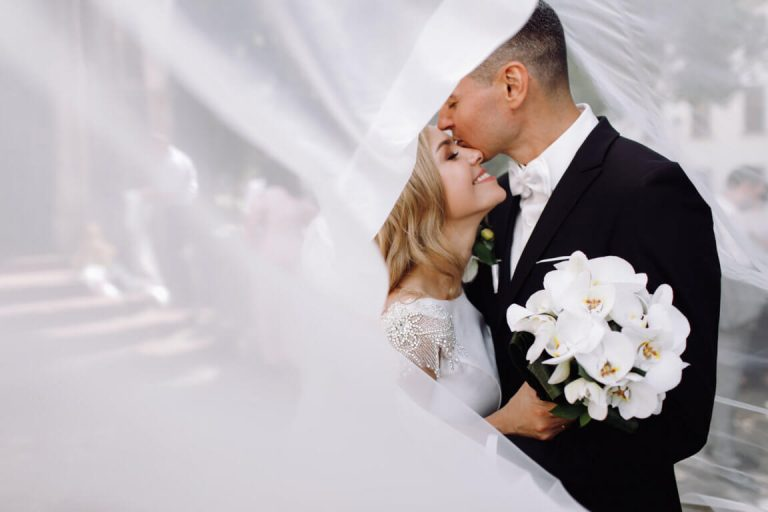 optimize- groom-black-tuxedo-hugs-tender-stunning-bride-while-they-stand