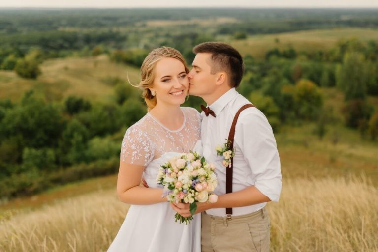 optimize- newlyweds-are-standing-against-beautiful-landscape-with-umbrella-groom-kisses-beautiful-bride-cheek